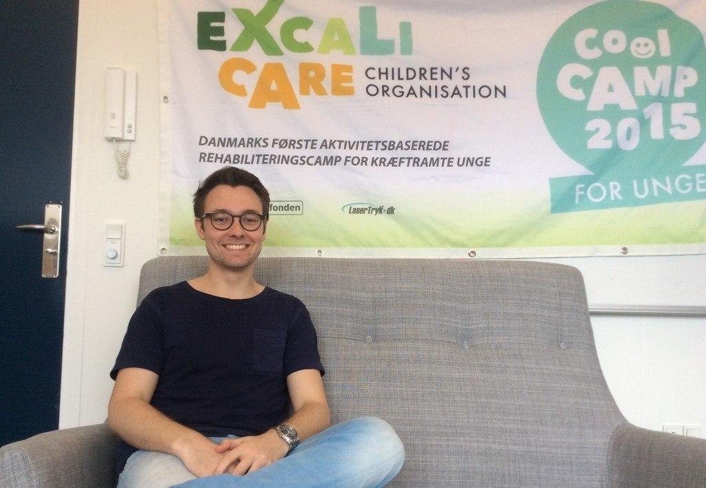 Billede af ExcaliCare's Rasmus Thøger Christensen siddende i en sofa med ExcaliCare's banner bag sig